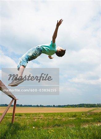 Boy Jumping off Trampoline