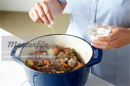 Woman Adding Flour to Beef Stew