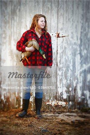 Teenage Girl holding Mallard Drake in front of Barn, Belledune, New Brunswick, Canada