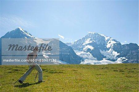 Woman Hiking using Walking Sticks, Bernese Oberland, Switzerland