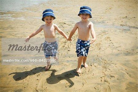 Twin Boys Walking Hand in Hand on Beach