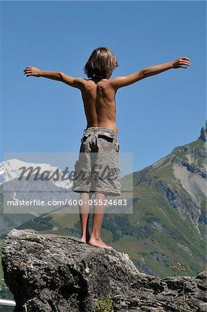 Back View of Boy Standing on Boulder, Alps, France