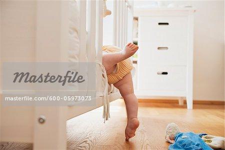 Baby Girl Climbing into Crib