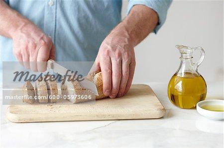 Man Slicing Baguette