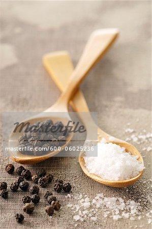 Rock Salt and Peppercorns in Wooden Spoons
