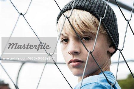Portrait of Boy Looking Through Chain Link Fence, Mannheim, Baden-Wurttemberg, Germany