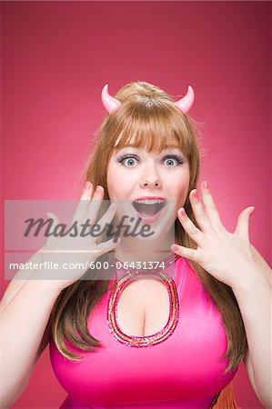 Portrait of Woman Wearing Devil Horns Making Faces