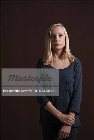 Portrait of Blond, Teenage Girl Looking at Camera, Studio Shot on Black Background