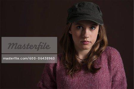 Close-up Portrait of Blond, Teenage Girl wearing Baseball Hat, Studio Shot on Black Background