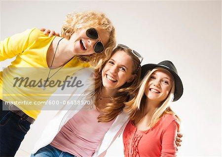 Portrait of Three, Cool Teenage Girls, Looking at Camera Smiling, Diagonal Studio Shot on White Background