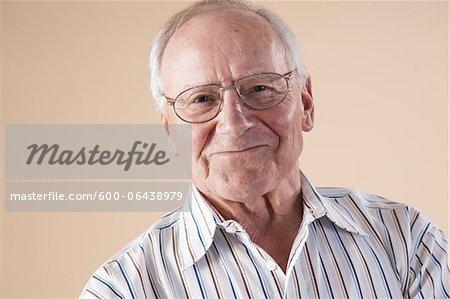 Portrait of Senior Man wearing Aviator Eyeglasses, Looking at Camera Smiling, in Studio on Beige Background