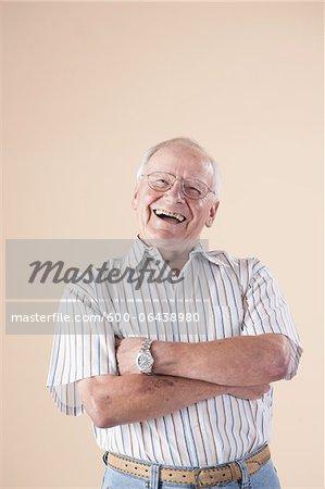Portrait of Senior Man wearing Aviator Eyeglasses, Looking at Camera Laughing, in Studio on Beige Background