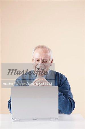 Senior Man Sitting at Table looking at Laptop Computer Laughing, Studio Shot on Beige Background