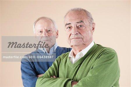 Portrait of Two Senior Men Looking at Camera, Studio Shot on Beige Background