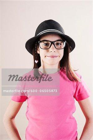 Portrait of Girl wearing Fedora and Horn-Rimmed Eyeglasses, Looking at Camera, Studio Shot