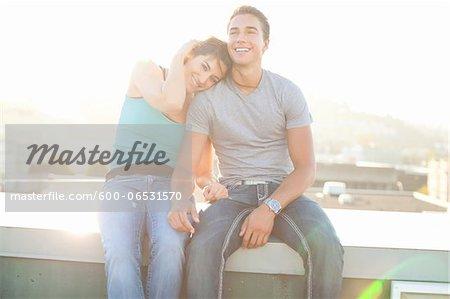 Portrait of Couple Sitting on Rooftop Outdoors, Portland, Oregon, USA