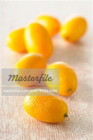 Close-up of Kumquats on Beige Background