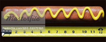 Hotdog with mustard beside measuring tape