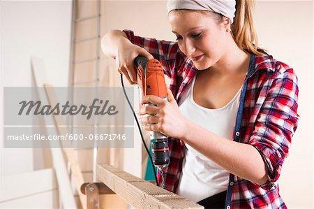 Studio Shot of Young Woman Drilling Lumber