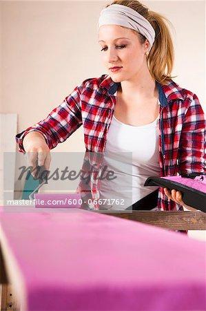 Studio Shot of Young Woman Painting Lumber