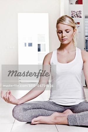 Young Woman doing Yoga in Lotus Pose and Akash Mudra