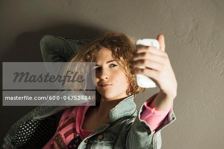 Teenage Girl taking Self Portrait with Camera Phone, Studio Shot