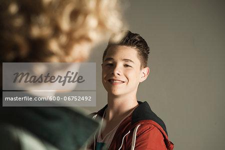 Teenage Boy smiling at Teenage Girl, Studio Shot