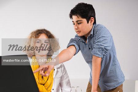 Teenagers looking at Laptop Computer, Studio Shot