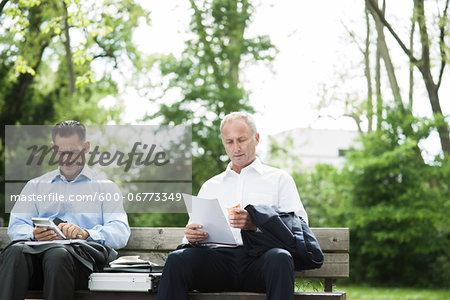 Businessmen working on Park Bench, Mannheim, Baden-Wurttemberg, Germany