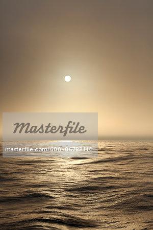 The Atlantic ocean illuminated off the coast of Nova Scotia in fog with the sun shining through.