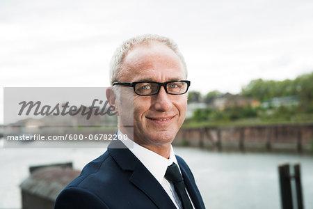 Portrait of mature businessman outdoors, wearing horn-rimmed eyeglasses, smiling at camera, Mannheim, Germany