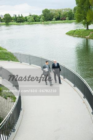 Mature businessmen on walkway talking, Mannheim, Germany