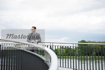 Mature businessman standing on bridge, Mannheim, Germany