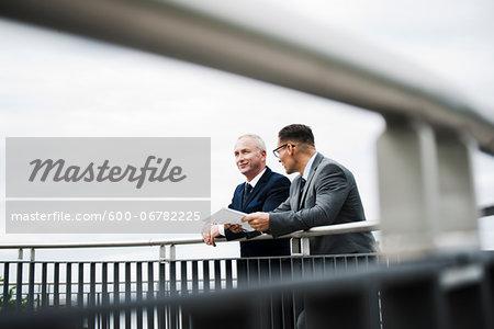 Mature businessmen standing on bridge talking, Mannheim, Germany