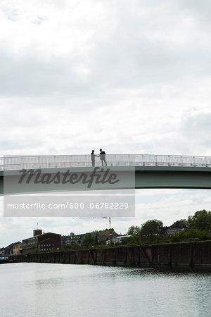 Silhouette of mature businessmen standing on bridge shaking hands, Mannheim, Germany