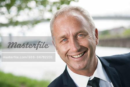 Close-up portrait of mature businessman smiling at camera
