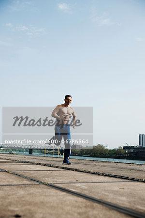 Mature man running along loading dock, Mannheim, Germany