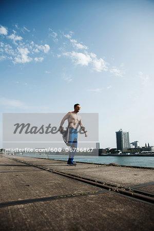 Mature man stretching on loading dock, Mannheim, Germany