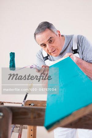 Senior Man Inspecting Painted Board, Studio Shot