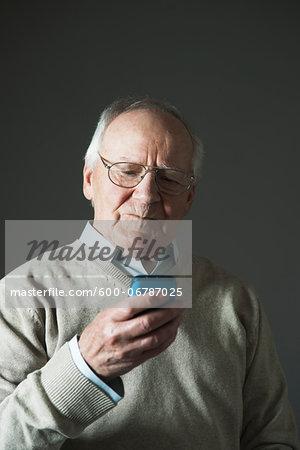 Elderly Man using Cell Phone in Studio