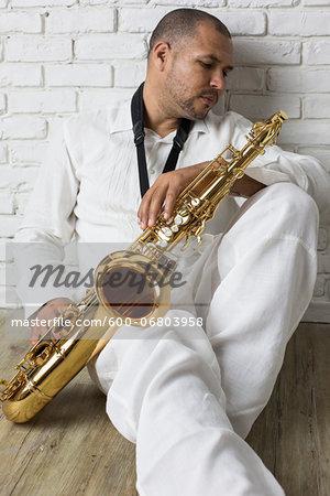 Portrait of Musician holding Saxophone, Studio Shot