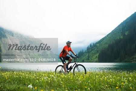 Mature Man Riding Mountain Bike by Vilsalpsee, Tannheim Valley, Tyrol, Austria