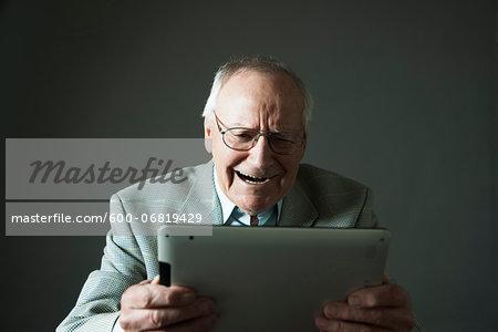 Senior Man using Tablet Computer, Studio Shot