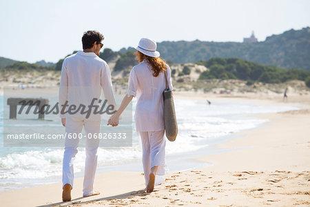 Back View of Couple Walking on Beach, Sardinia, Italy
