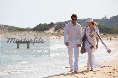 Young couple walking at the beach during summer holidays, Cala Cipolla, Chia Bay, Sardinia, Italy