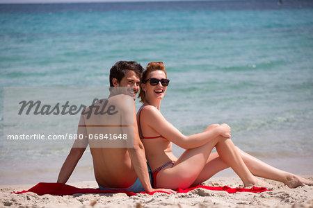 Young couple relaxing at the beach during summer holidays, Cala Cipolla, Chia Bay, Sardinia, Italy