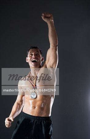 Muscular Man with Medal around Neck Cheering, Studio Shot