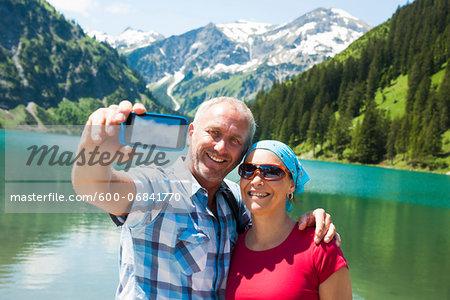 Couple taking Self Portrait by Lake, Vilsalpsee, Tannheim Valley, Tyrol, Austria