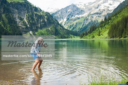Mature man skipping stones at Lake Vilsalpsee, Tannheim Valley, Austria