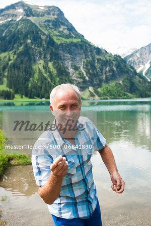 Portrait of mature man skipping stones at Lake Vilsalpsee, Tannheim Valley, Austria